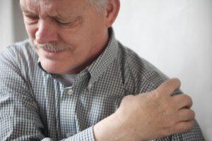 Oudere man met schouderklachten houdt zijn schouder vast met zijn hand en trekt een pijnlijk gezicht