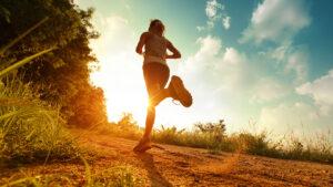 Een sporter die aan het hardlopen is bij een ondergaande zon