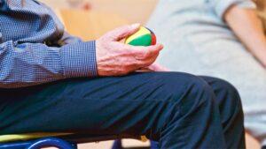 Oudere man met een oefenballetje in zijn hand.