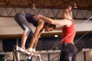 Vrouw staande op en gymtoestel ongelijke brug wordt ondersteund tijdens een oefening