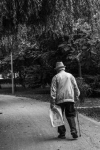 Oudere man met een wandelstok loopt op een weggetje