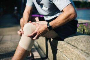 Man met knieklachten heeft een ingezwachtelde knie zittend op een muurtje heeft zijn handen op zijn knie