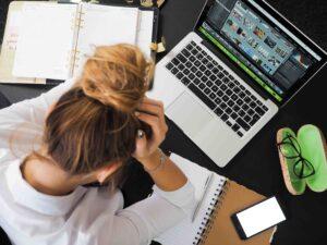 Vrouw zit aan een bureau met latop en heeft haar hoofd in haar handen
