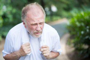 Oudere man staat buiten adem voorovergebogen