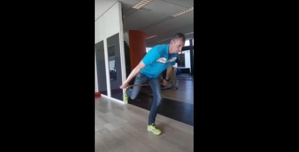 Sport actief trainer staat op 1 been te balanceren en gebruikt een stok voor een uitdagende challenge