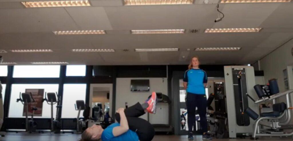 Oefeningen op een fitnessmatje voorgedaan door 2 Sport actief trainers