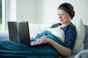 Vrouw met kanker liggend in bed werkt op een laptop